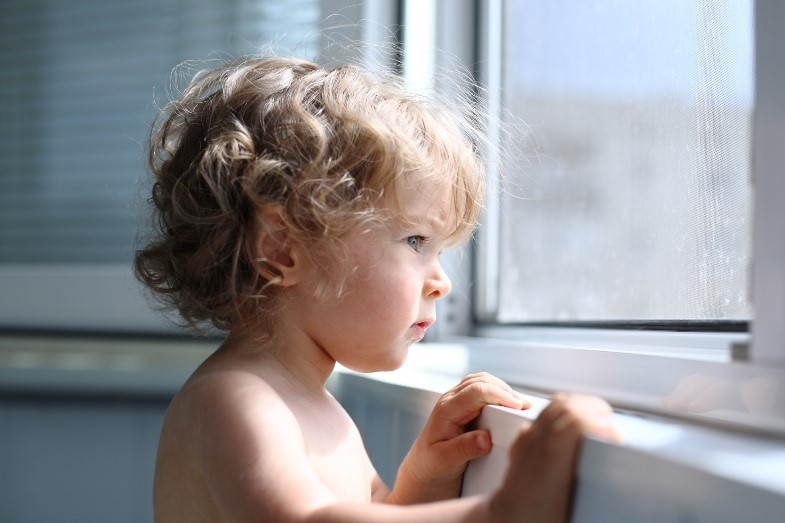 enfant qui regarde depuis sa tour montessori